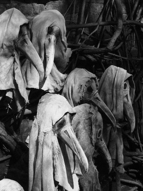 Masks worn by doctors during the Plague. The protective suit of the plague doctor consisted of a heavy fabric overcoat that was waxed, a mask with glass eye openings and a cone nose shaped like a beak to hold scented substances and straw
